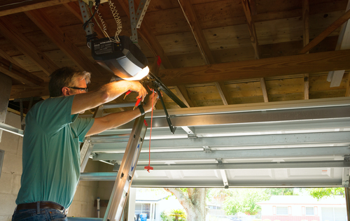 A technician works on a garage door opener