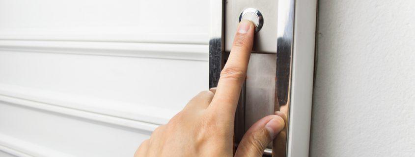 Hand pushing garage door button