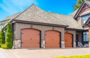 three garage doors driveway home